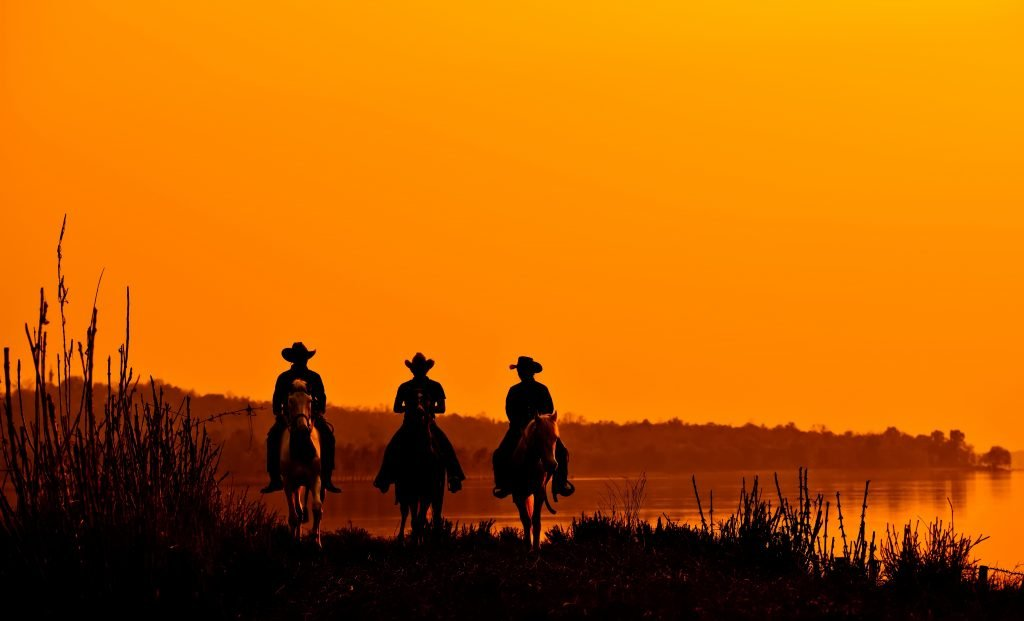 3 men on horseback riding into an orange sunset, a common sight in western movies about texas