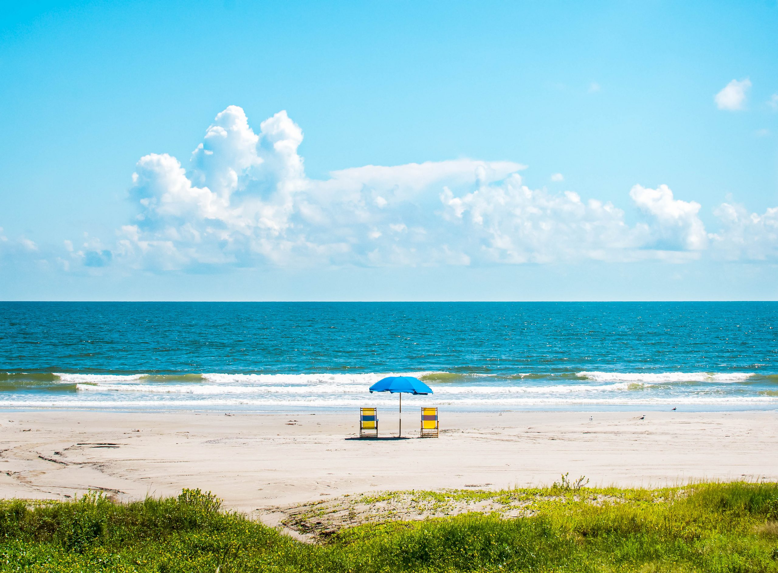two beach chairs with umbrella on a galveston beach, one of the best beaches near houston texas