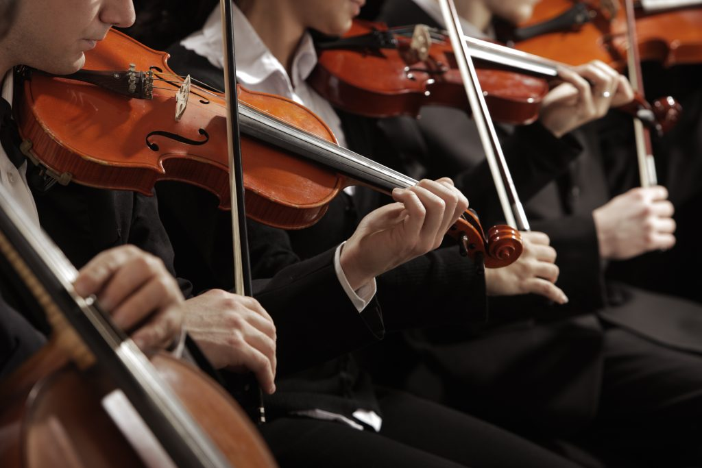 close up on violinists in an orchestra. the dallas symphony orchestra is one of the romantic date ideas in dallas tx