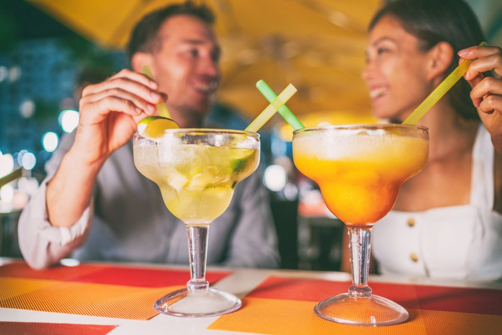 couple posing with margaritas. margarita mile is one of the fun romantic things to do in dallas for couples