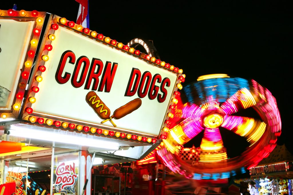 sign for corn dogs and a ferris wheel in the background lit up at night on a fairground