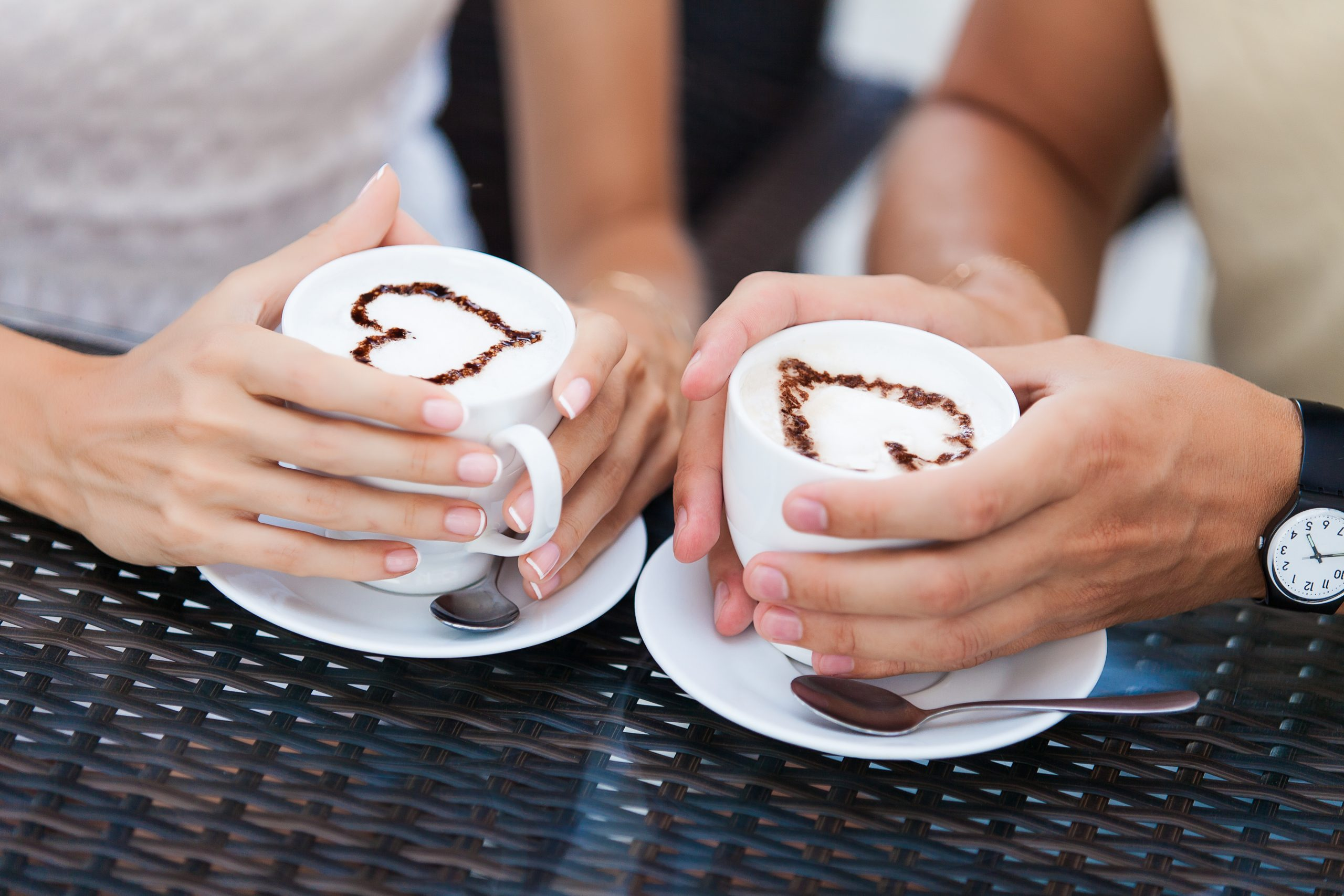 couple holding lattes with hearts on them--some of the best dallas date ideas and romantic things to do in dallas for couples include stopping for coffee