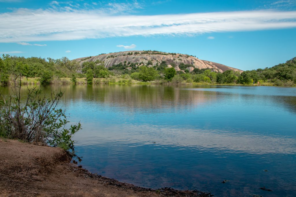 moss lake with enchanted rock visible across it