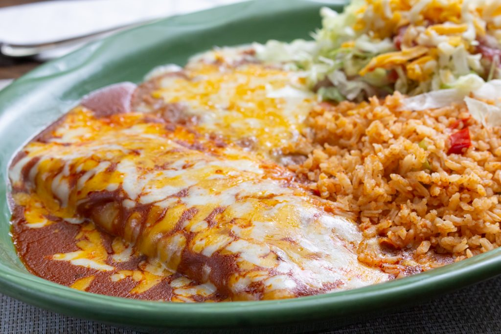 green plate with a texmex burrito and sides. what is texas known for includes lots of texmex dishes