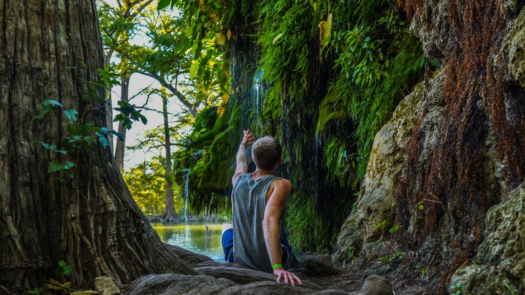 man in a tank top sitting in front of a waterfall at krause springs, one of the best things to do in spicewood texas