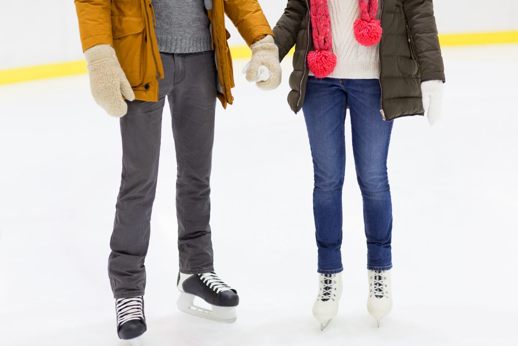 couple ice skating on an indoor rink, photo taken from the waist down. ice skating is one of the romantic things to do in dallas for couples