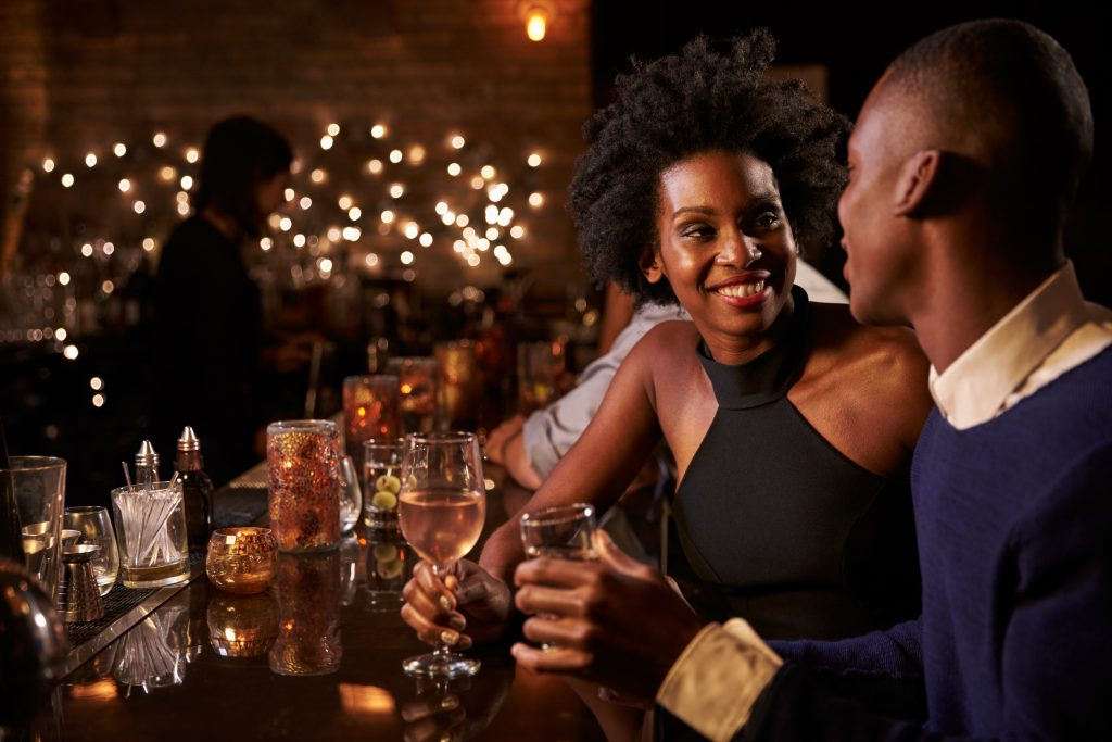 couple getting drinks at a bar, with wine glasses in hand