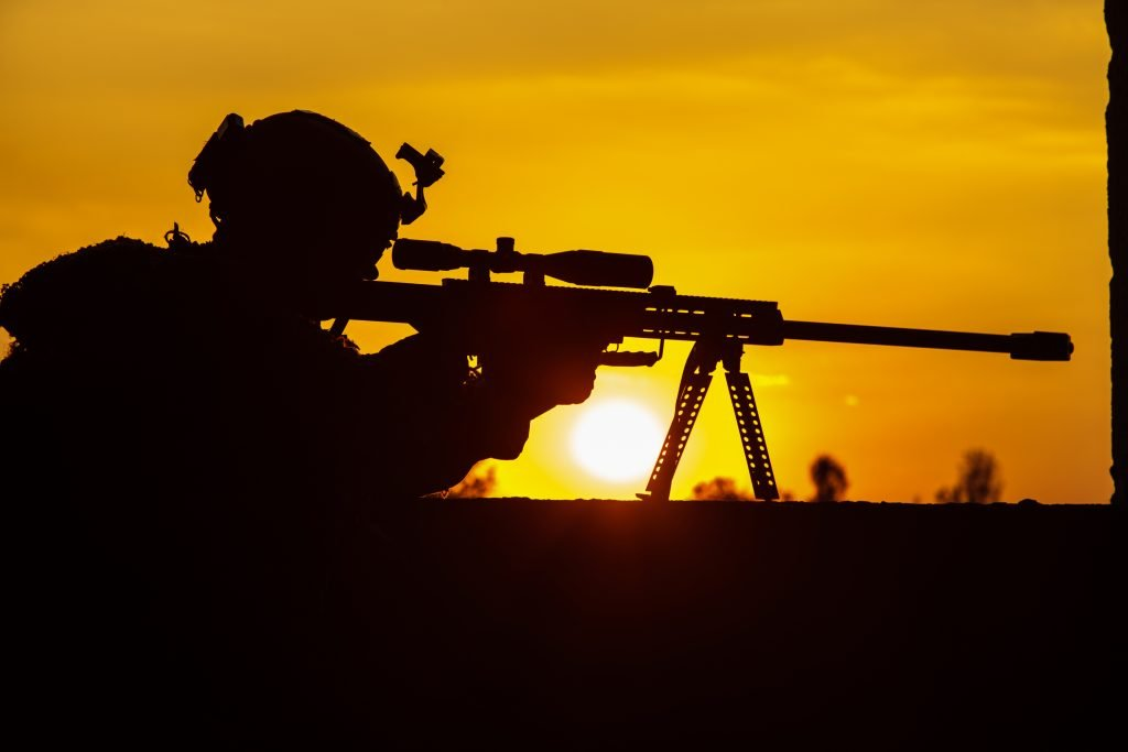 sniper in silhouette set against a orange sunset