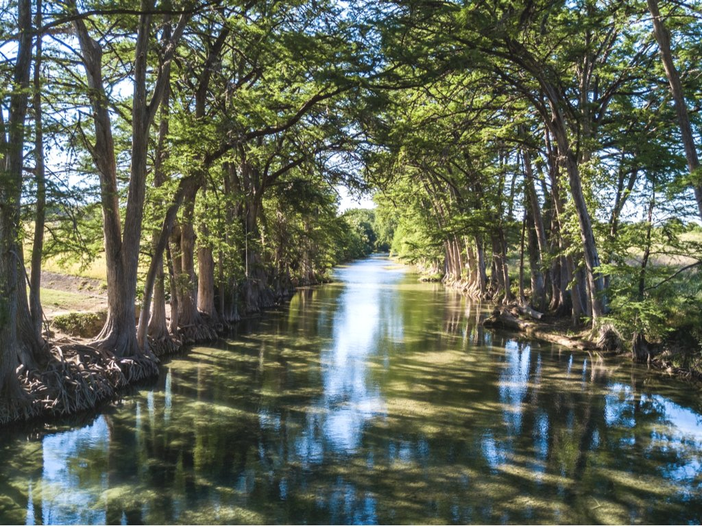 medina river in texas tubing spot lined with trees
