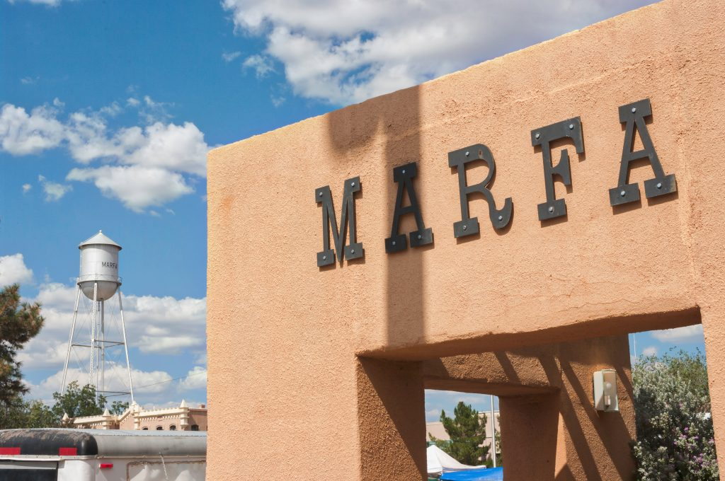 "adobe building reading ""marfa"" with the water tower in the background. visiting marfa is one of the fun things to do in west texas"