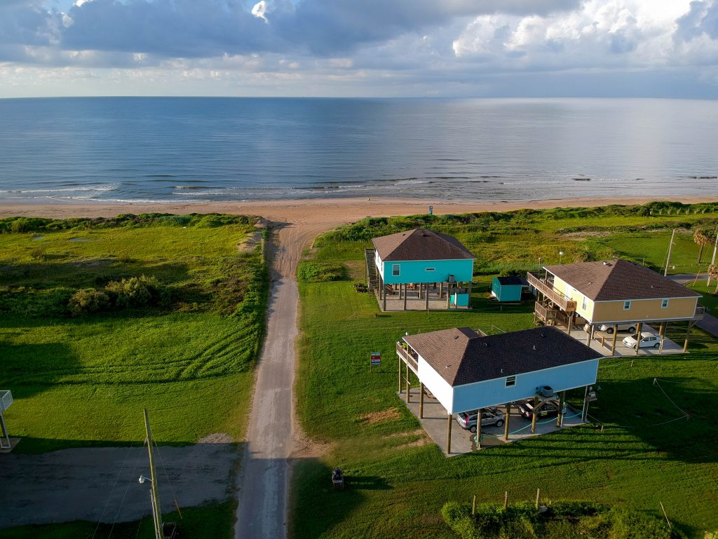 beach on bolivar peninsula with beach houses in the foreground, one of the best beaches near houston texas