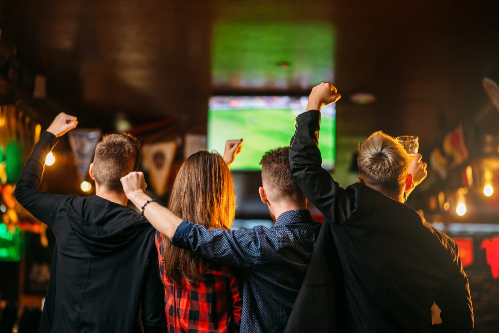 group of peope cheering on a sports game at a bar, what is texas known for includes famous sports teams