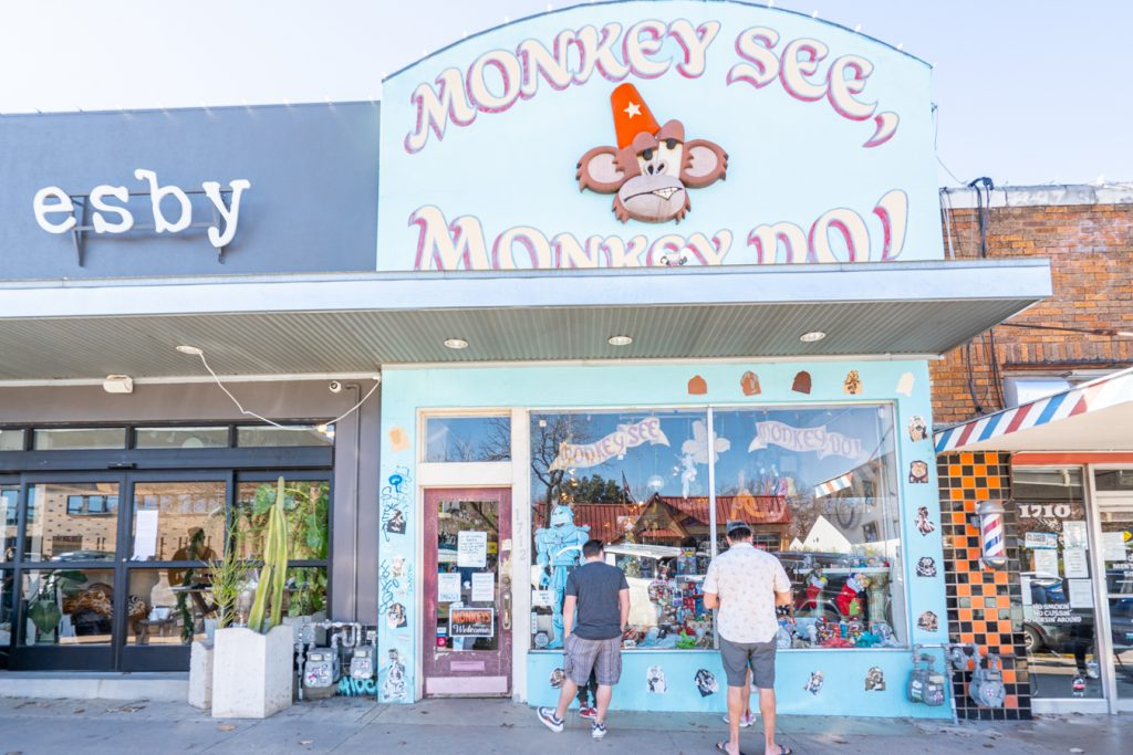 two men standing in front of monkey see monkey do south congress boutiques