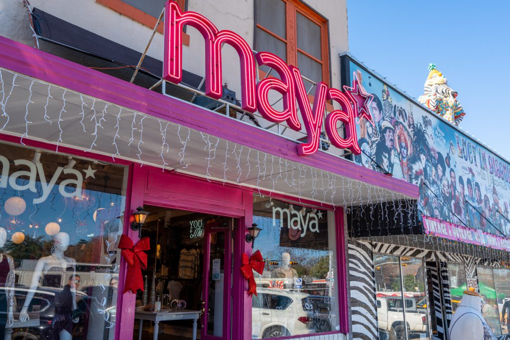 "front facade of maya star in austin with ""maya"" in pink letters out front"