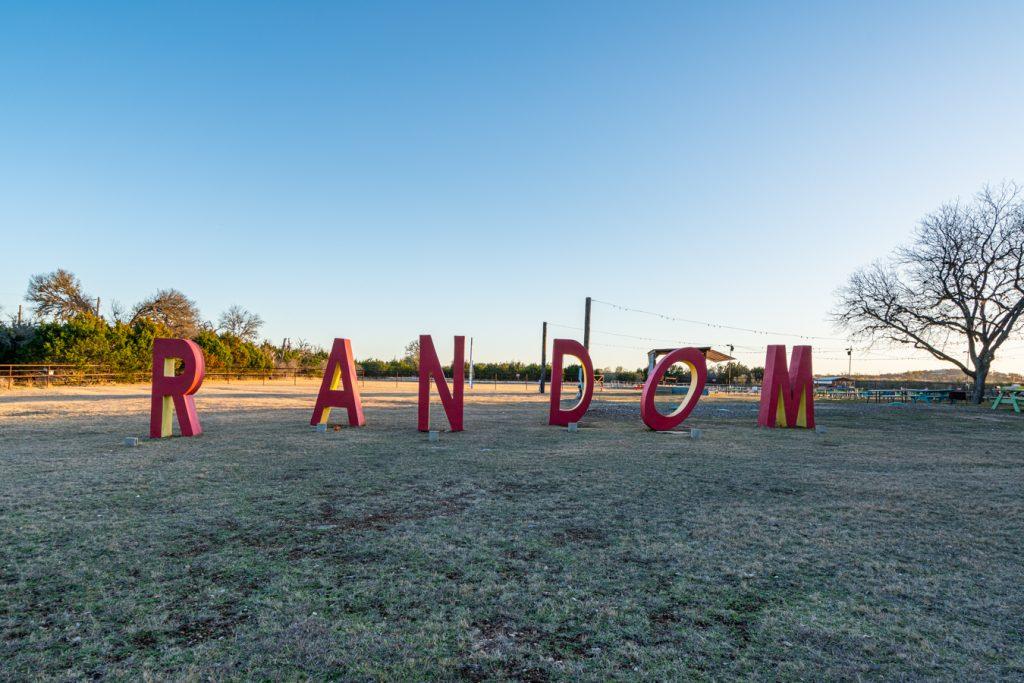 "red letters spelling ""random"" at random beer garden at sunset"