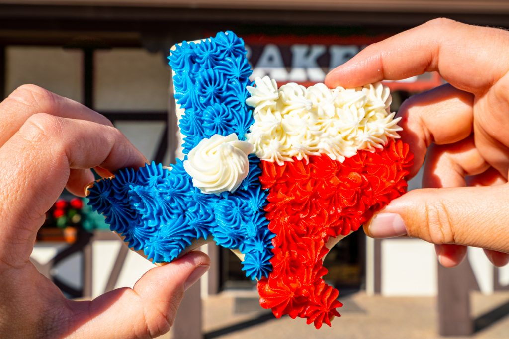 frosted cookie in the shape of texas being held up in front of a bakery