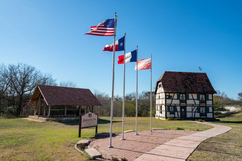 castroville texas visitors center with 4 flags flying in front of it