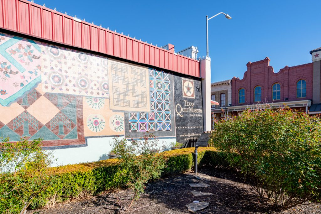 quilt mural on the side of the texas quilt museum, as seen from a small park