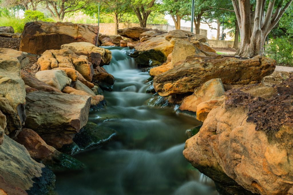 view of a waterfall in central park frisco, one of the best day trips from fort worth tx