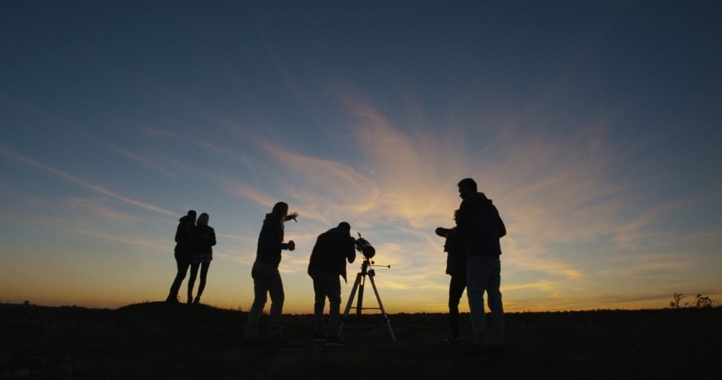 group of people with a telescope waiting for the sun to set for stargazing texas