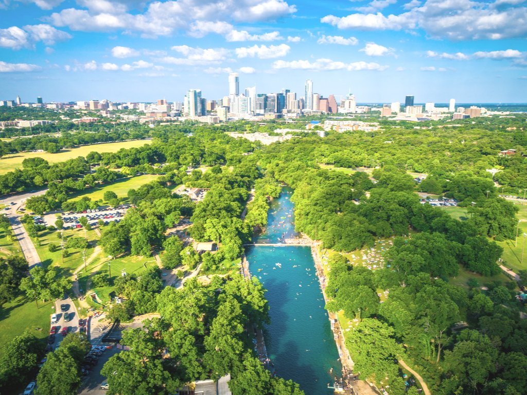 austin texas skyline aerial photo with barton springs pool in foreground, one of the best places to swim in austin tx