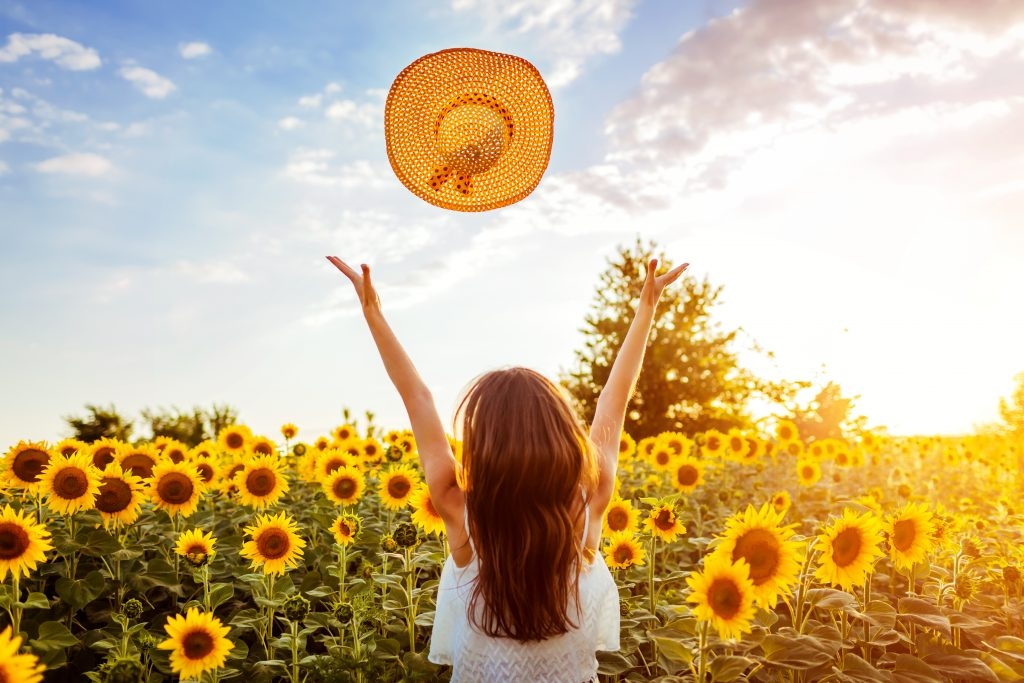 young woman throwing a hat into the air in front of one of the sunflower fields in texas