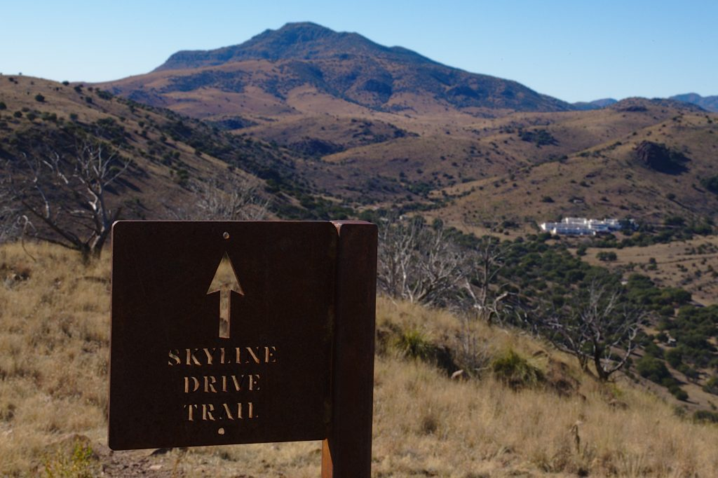 """metal sign stating """"skyline drive trail"""" with davis mountains texas in background"""