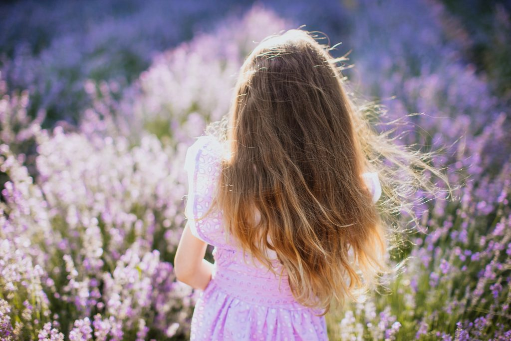 young girl standing in field of lavender texas with her back to the camera