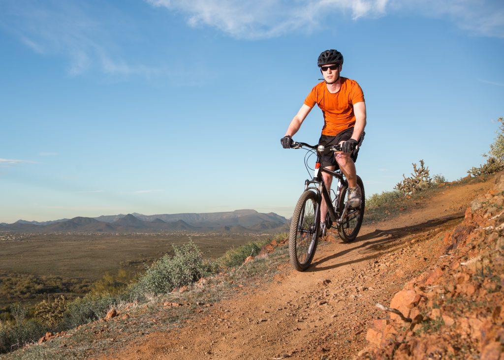 man in an orange shirt mountain biking in the desert