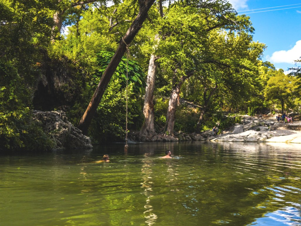 couple swimming in austin texas in a natural pool
