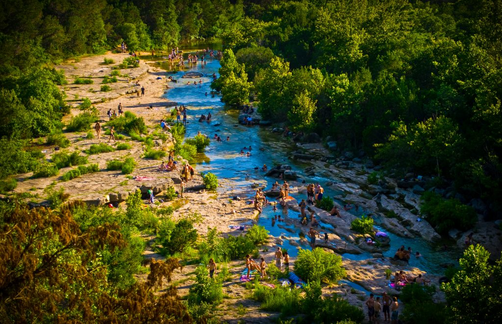 crowd of people swimming on the greenbelt austin