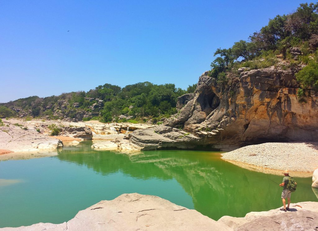 man standing on the banks of pedernales river, one of the best tx hill country places to see