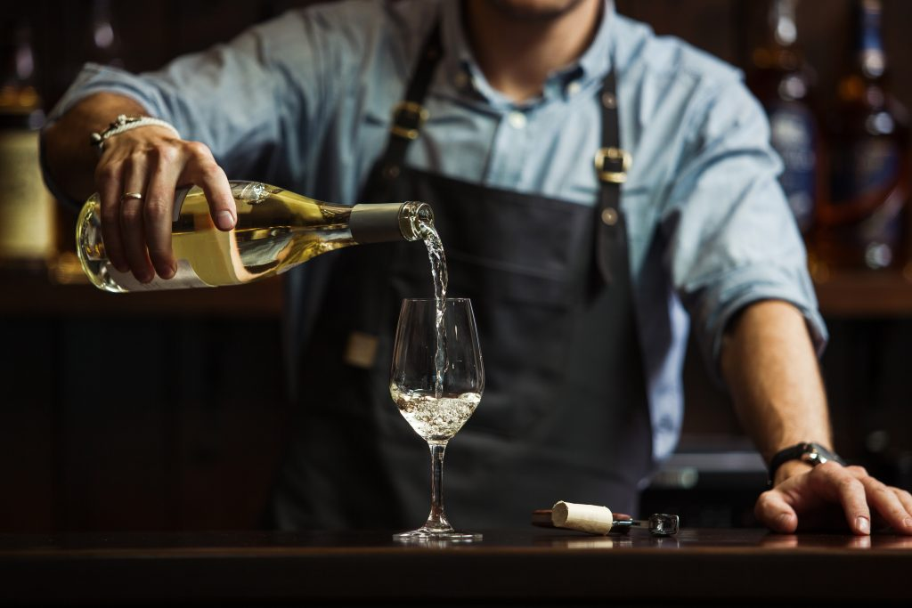 man in an apron behind a bar pouring a glass of white wine