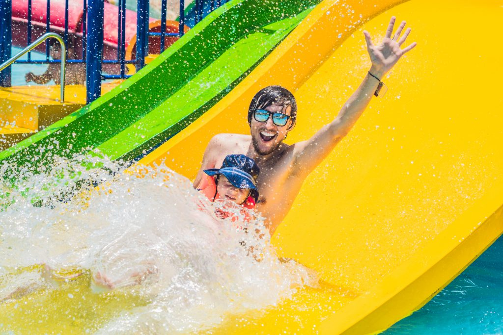 father and baby on a yellow waterslide