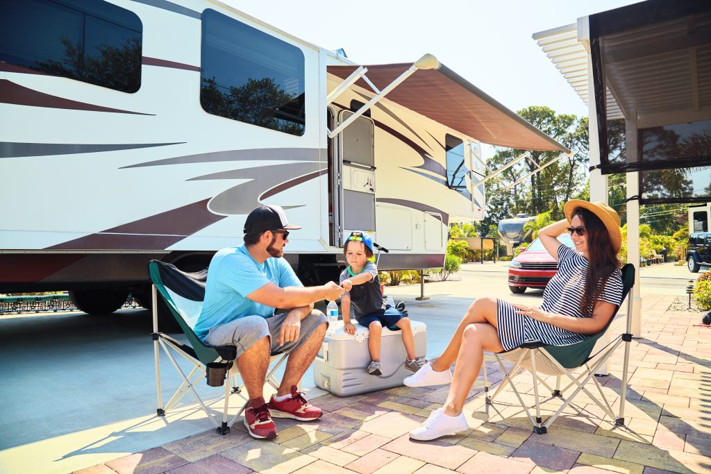 parents with their child sitting outside an rv in an rv park