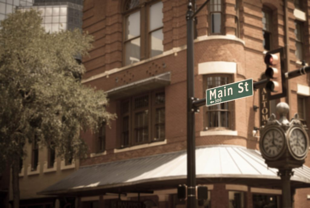 green sign for main street fort worth in front of an ornate building downtown