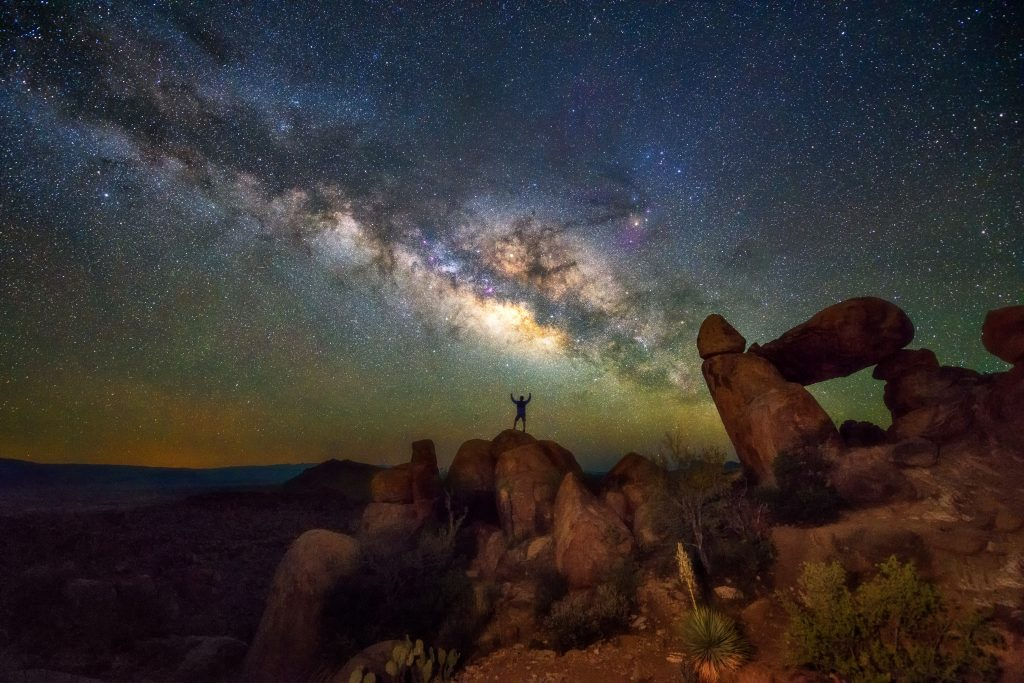 man standing on a boulder under the milky way stargaze in texas