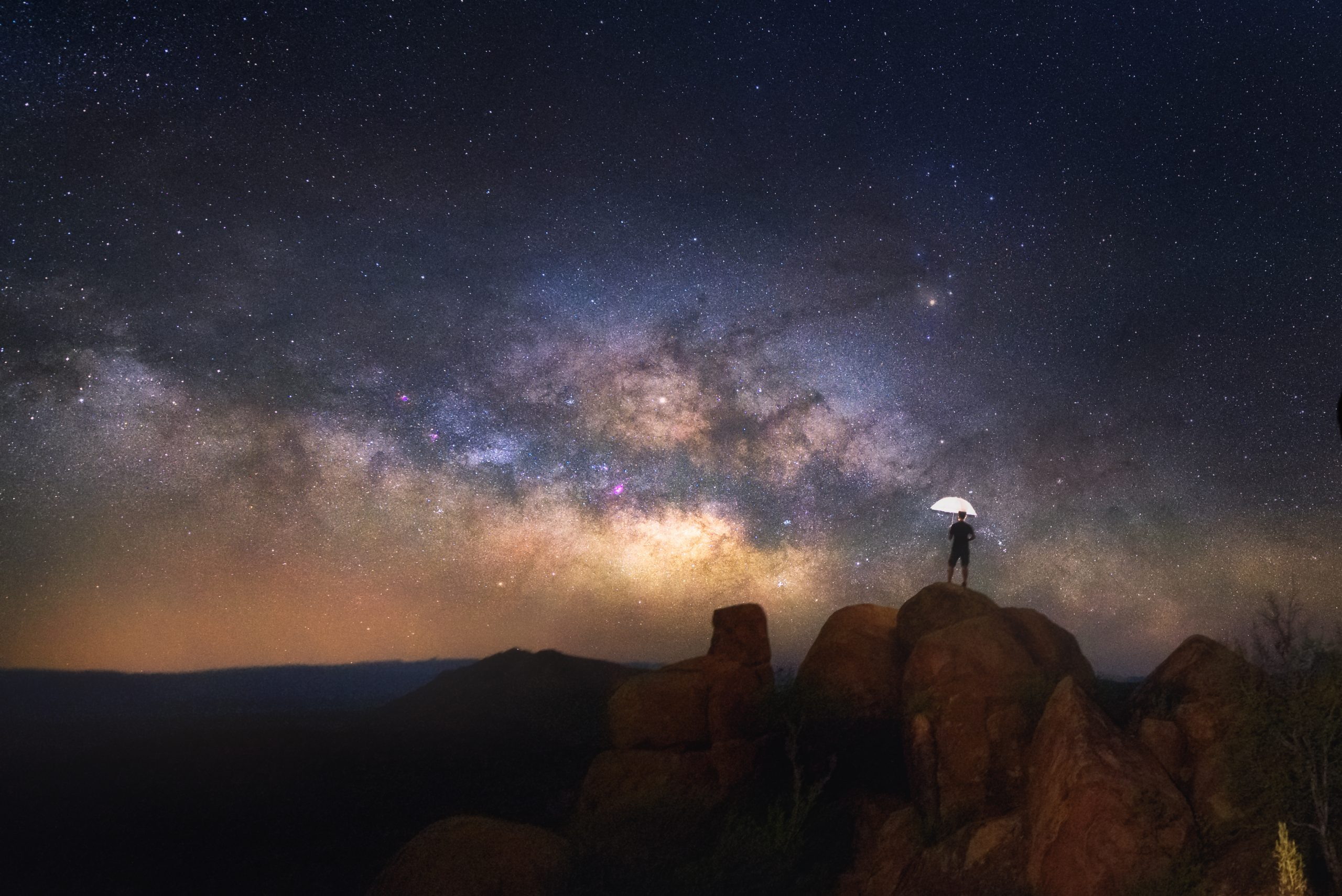 man standing on a boulder in west texas, enjoying some of the best stargazing in texas with milky way in background