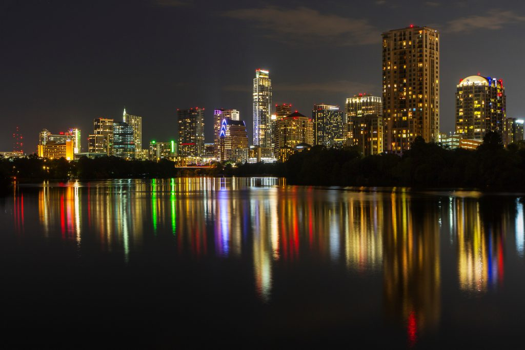 lights of downtown austin at night reflecting onto lady bird lake
