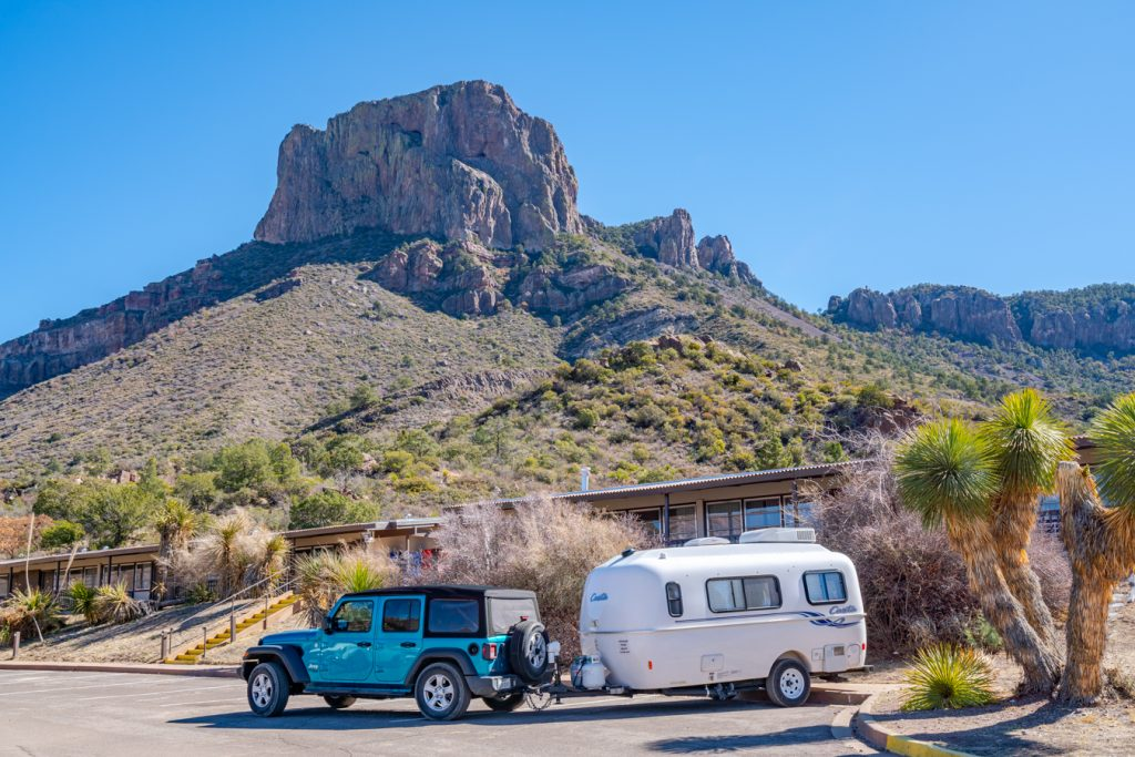 small rv in big bend national park chisos basin, being towed by a blue jeep