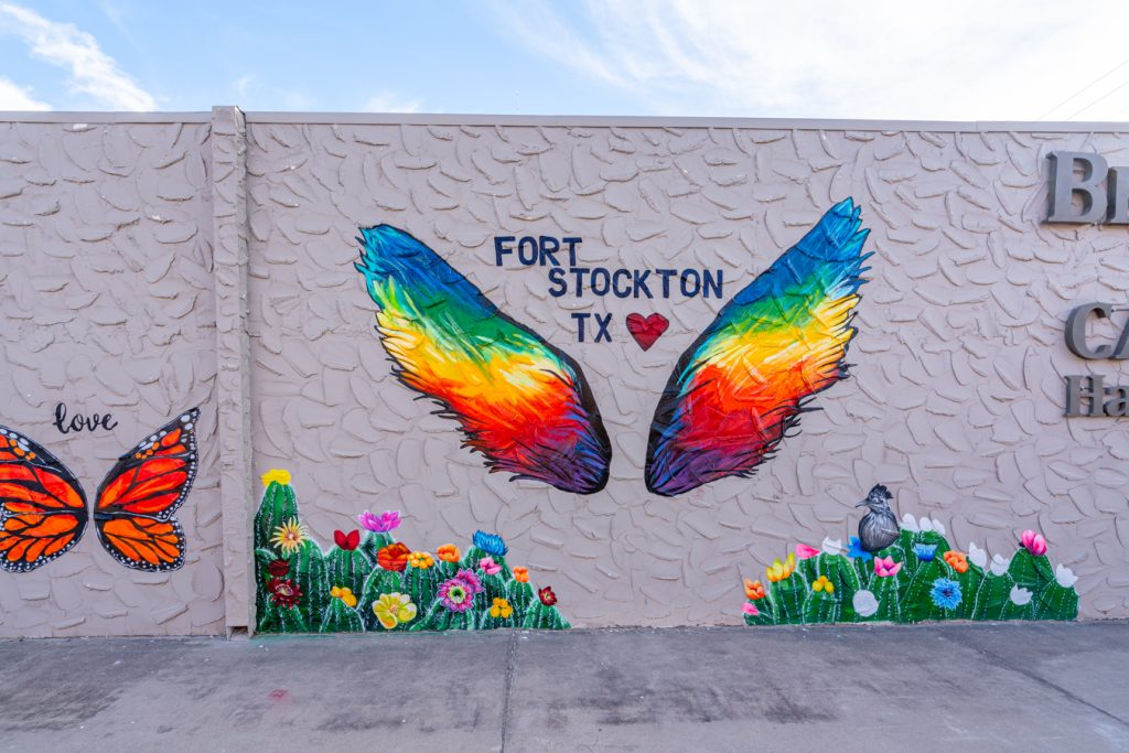 colorful mural of rainbow wings painted on a wall, reads fort stockton tx
