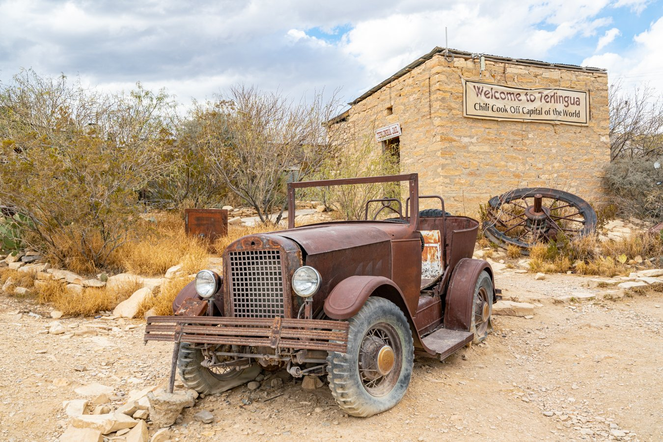 abandoned car parked in front of historic terlingua jail, one of the most famous ghost towns in texas