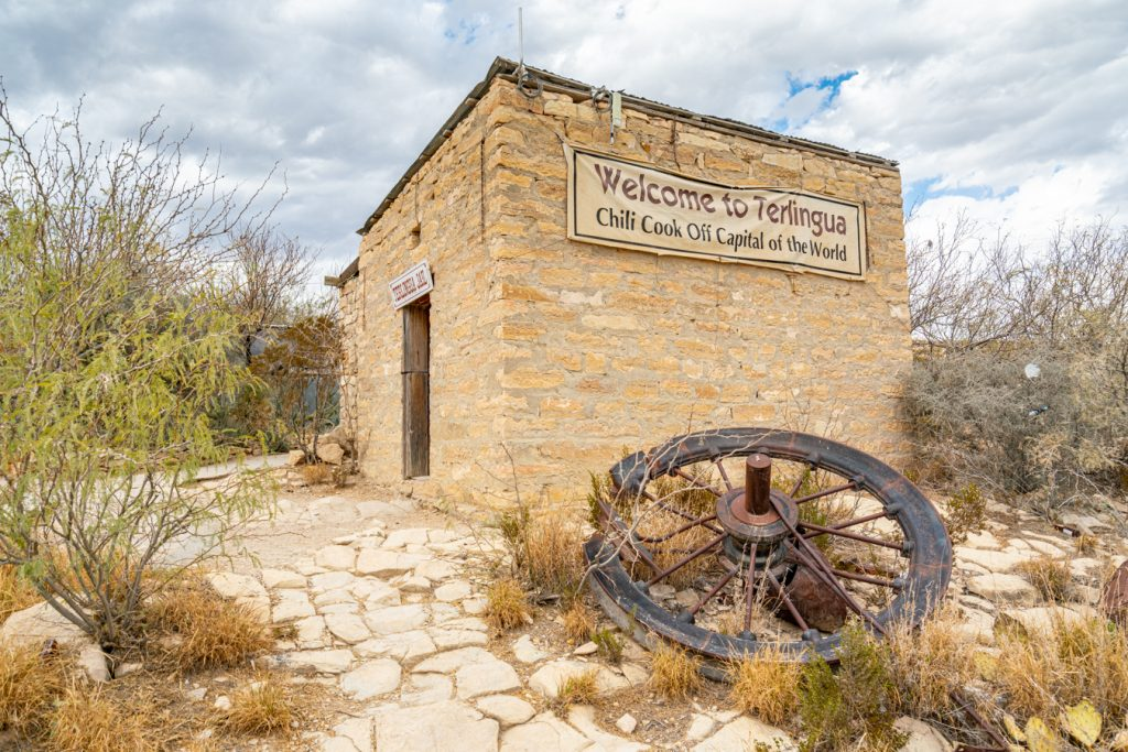 terlingua jail with a wooden wheel in front of it