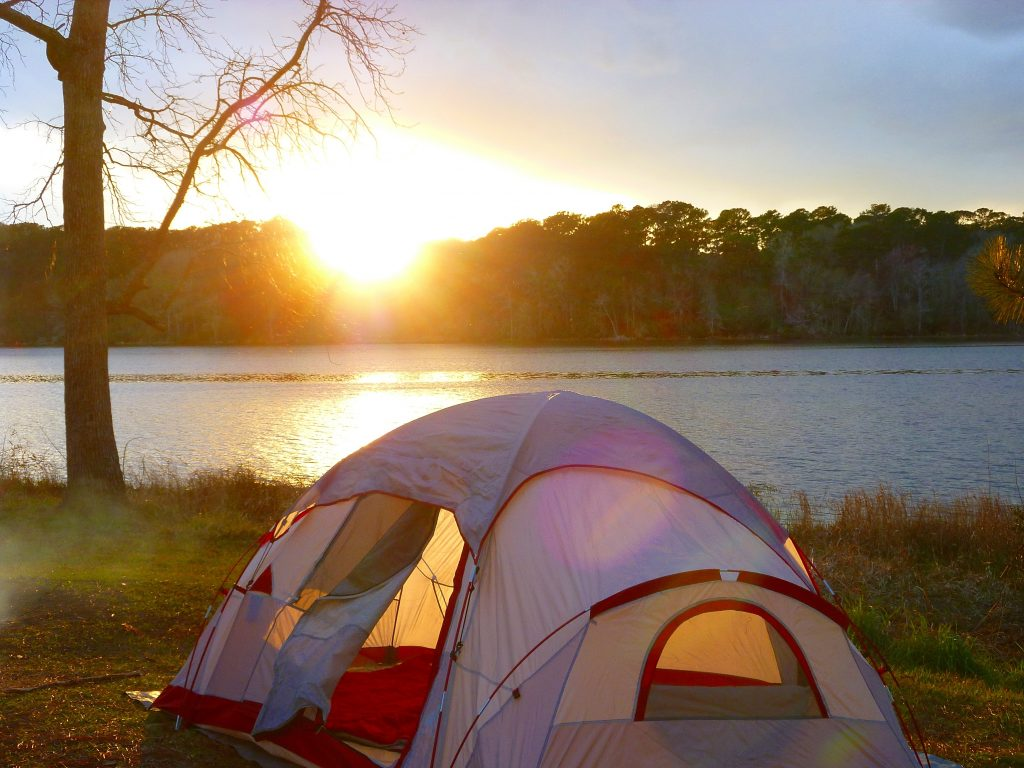 tent set up in front of raven lake near houston at sunset