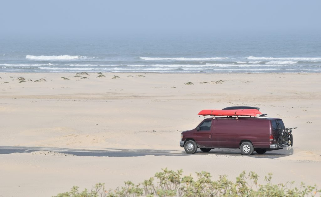 maroon van with a red kayak on top driving on a texas beach