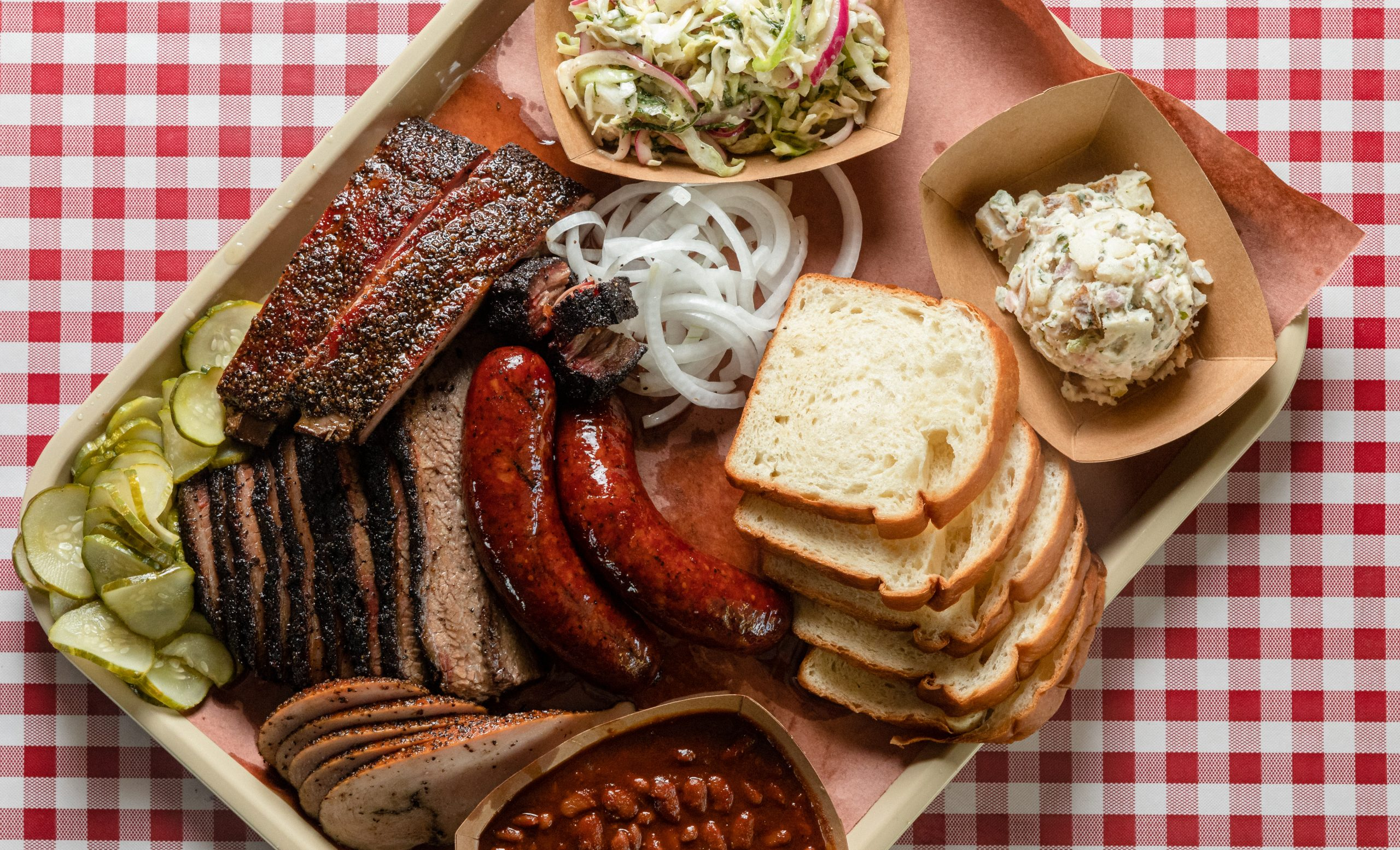 tray of texas bbq featuring brisket ribs sausage as seen from above