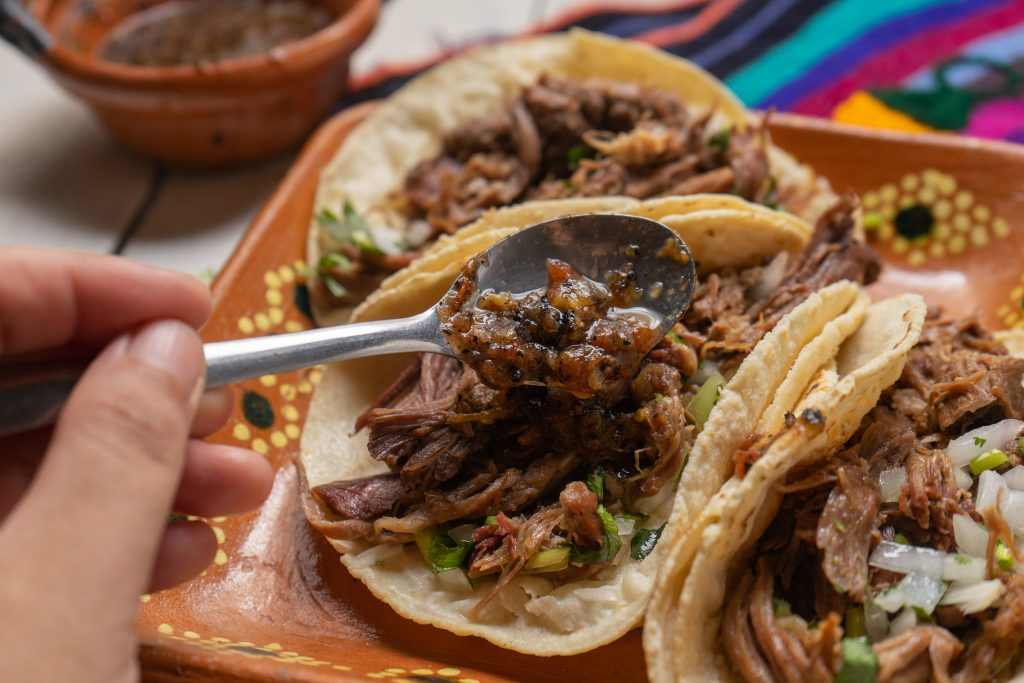 3 barbacoa tacos on an orange plate