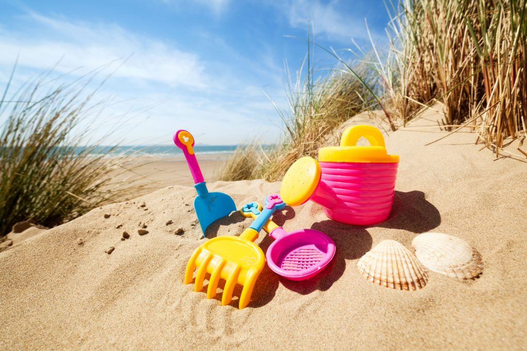 collection of colorful childrens sand toys on a beach