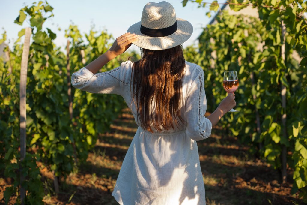 woman in a white dress in the grape vines of a vineyard