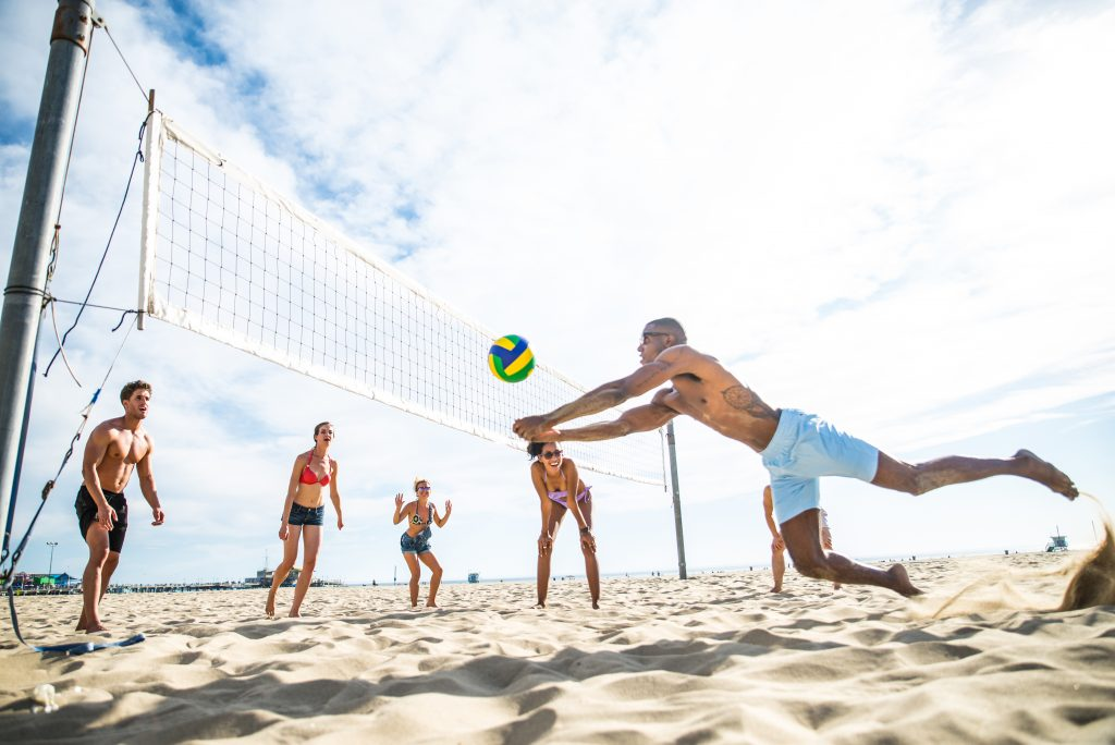 group of people playing volleyball on the beach